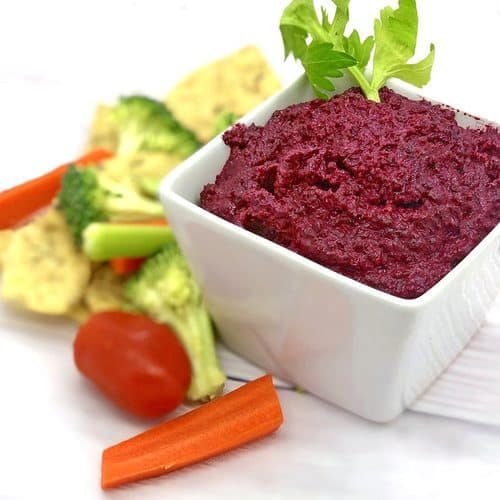 Beet Hummus with Veggies on a white background