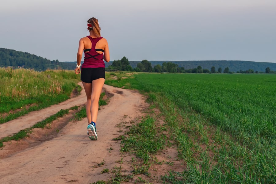 Athletic Blonde Teenage Girl Running At Dirt road In field. Sport girl running outdoor. Young woman running in field. Back view running lass on meadow at sunset. Fitness training.