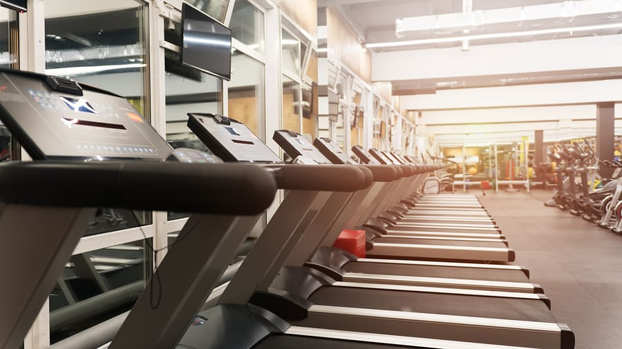 Fitness gym club with row of treadmills for fitness cardio training. Healthy lifestyle concept. Modern gym interior with equipment.