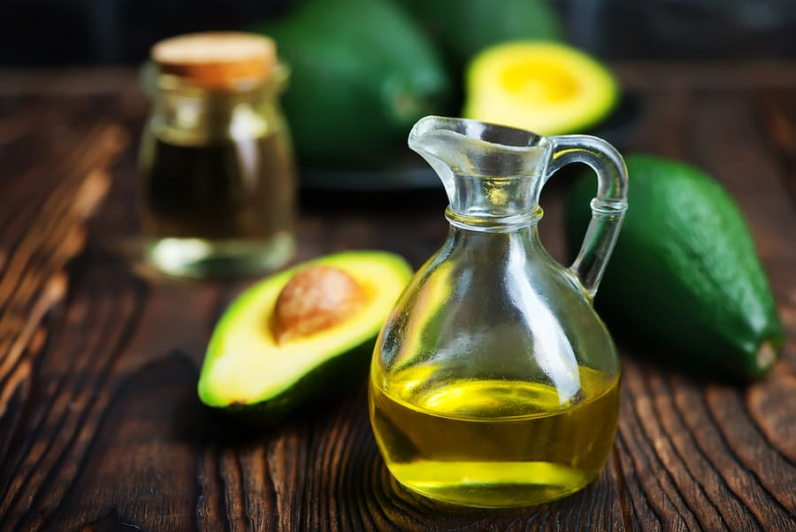 Avocado oil and avocado on wooden board