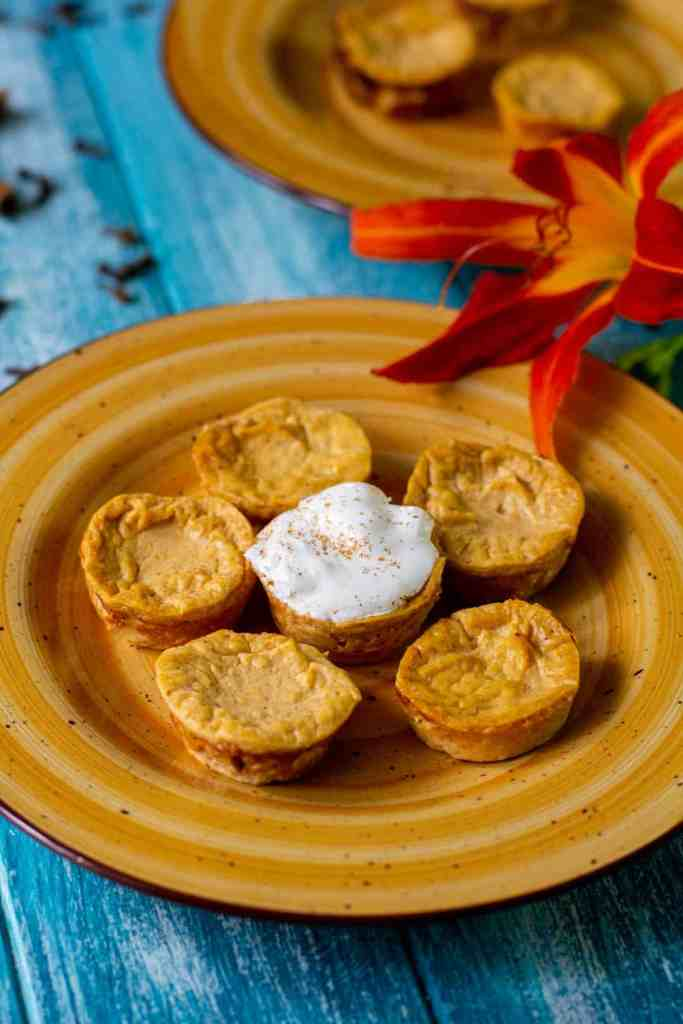 Healthy pumpkin cheesecake bites on an orange plate with a blue background
