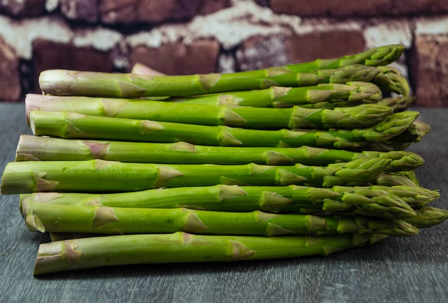 uncooked Fresh green german asparagus on a wooden table