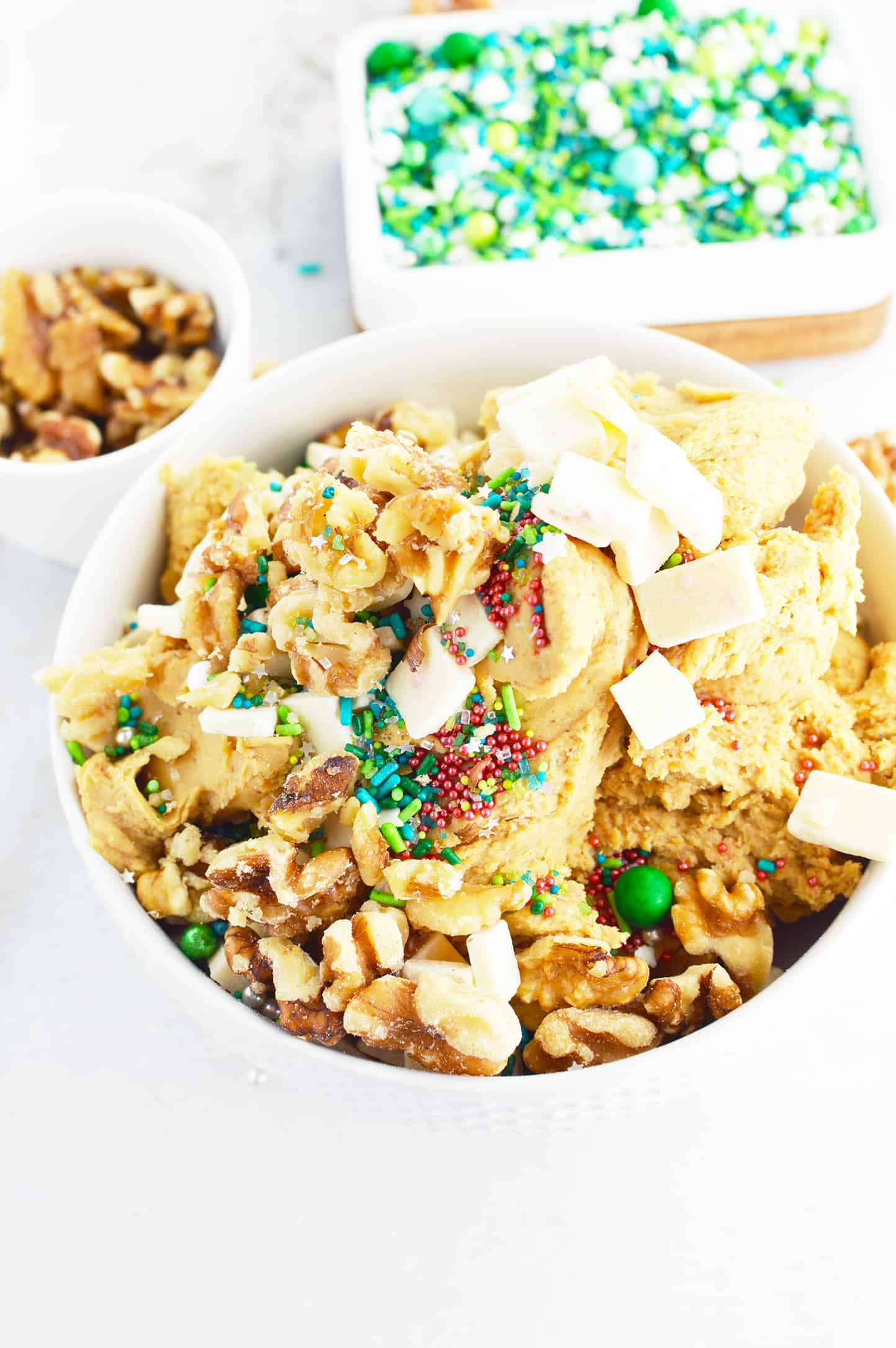 Healthy Edible Cookie Dough with holiday sprinkles and walnuts in the background.