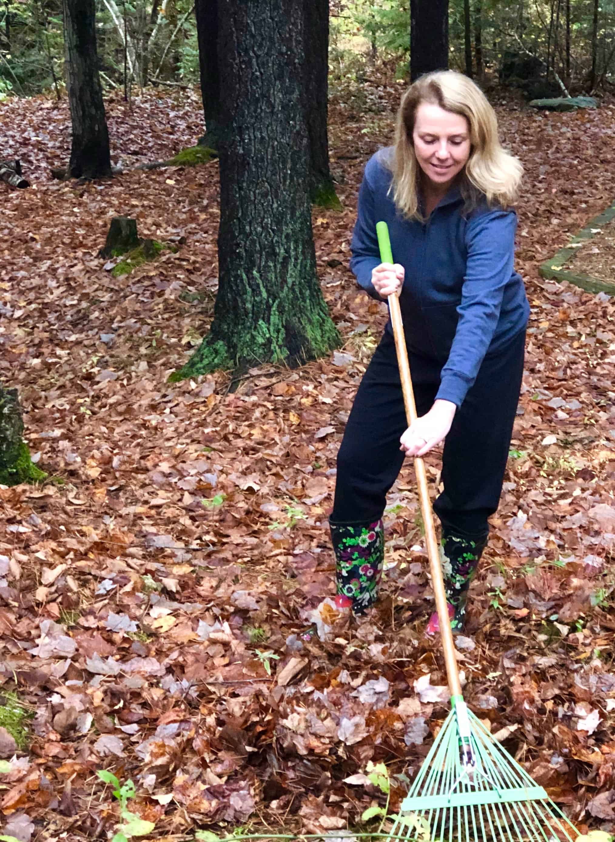 Beautiful blonde woman in sweatpants raking leaves in Maine.
