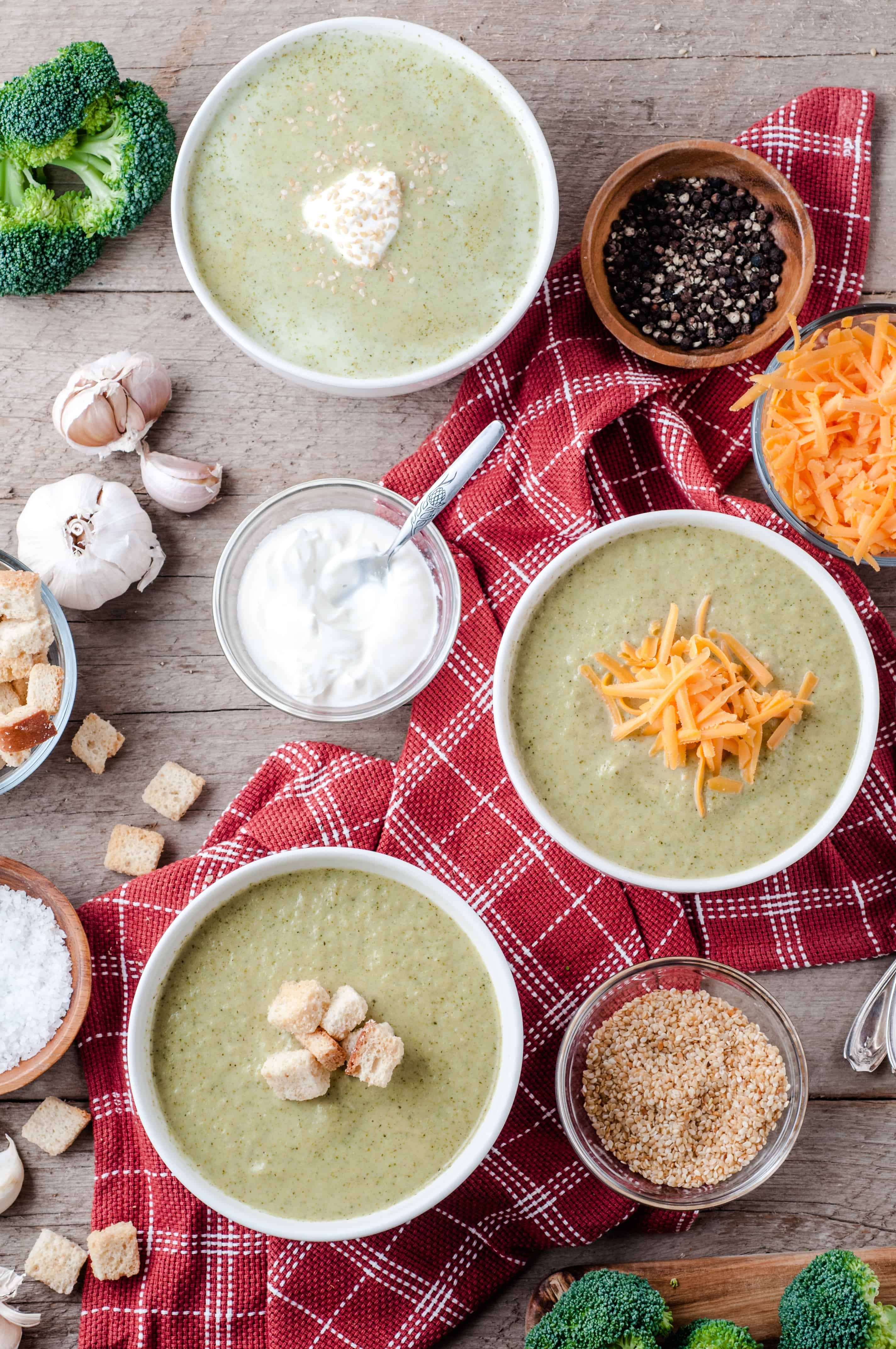 3 bowls of Vegetarian Cream of Broccoli soup with toppings.