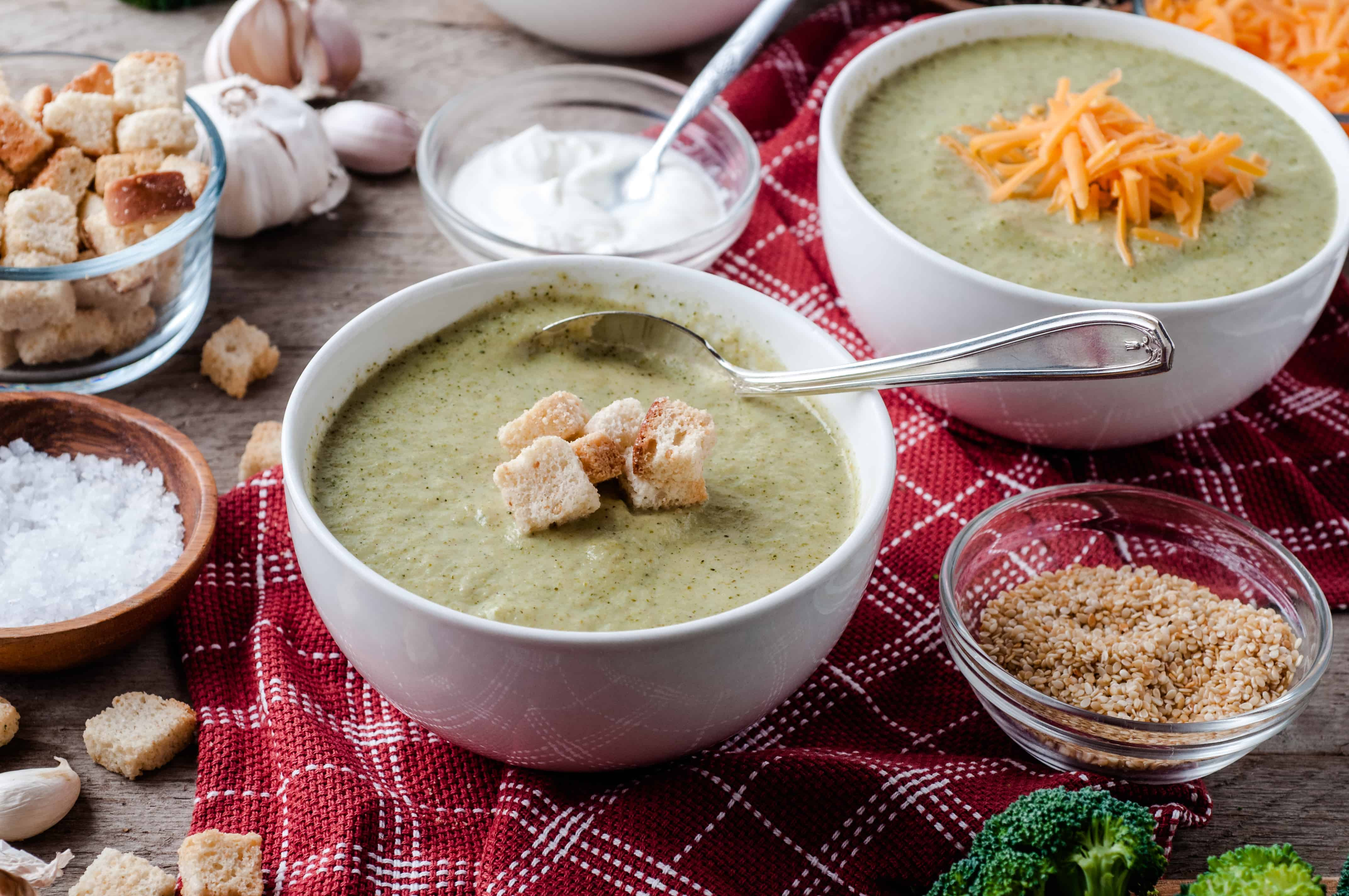 2 bowls Vegetarian Cream of Broccoli soup with toppings on them.
