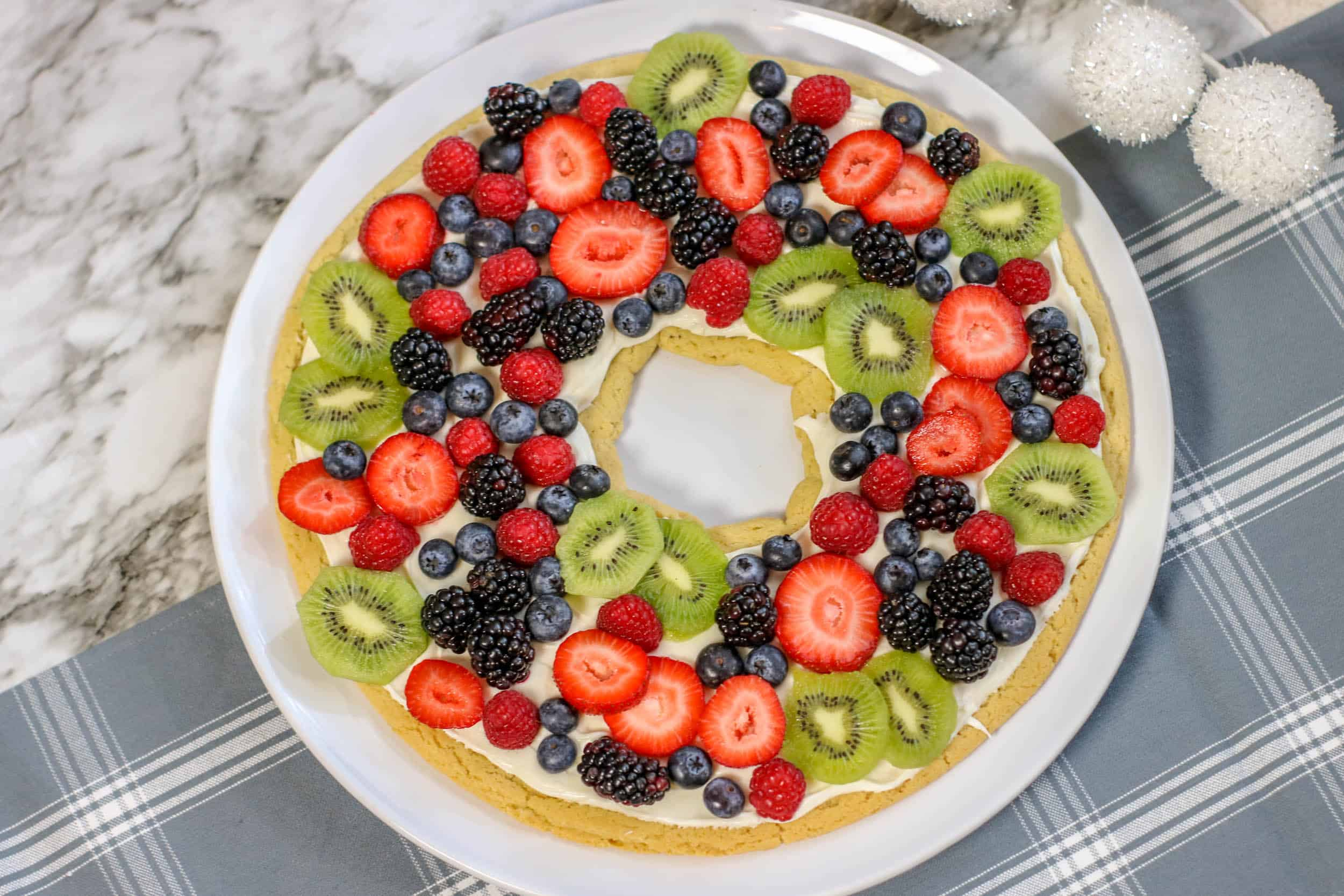 Fruit Pizza Christmas Wreath on light t=blue table cloth.