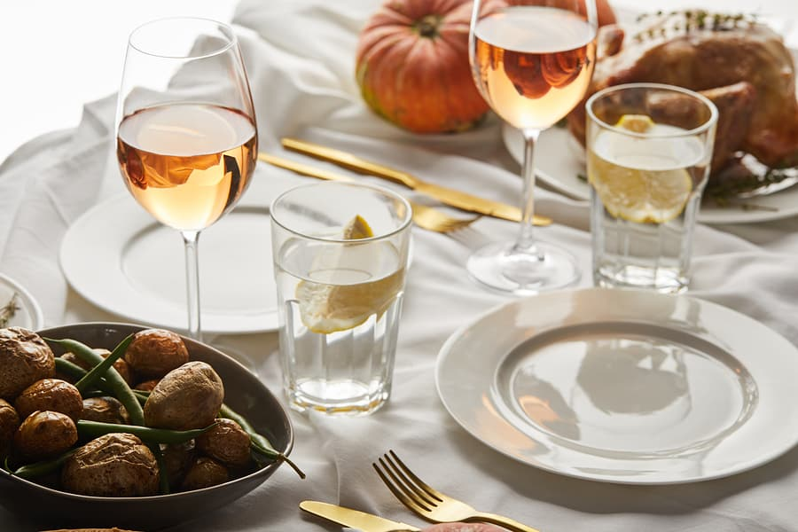 festive thanksgiving dinner with baked vegetables, glasses with rose wine and whole pumpkins on white marble table