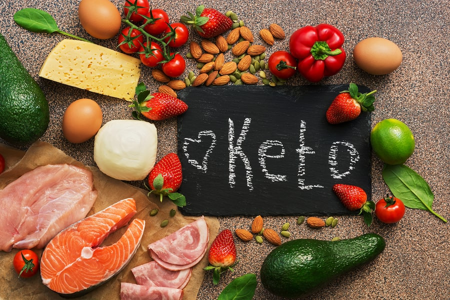 Keto diet food. Healthy low carbs products.Keto diet concept. Vegetables, fish, meat, nuts, seeds, strawberries, cheese on a brown background. Top view. Signboard