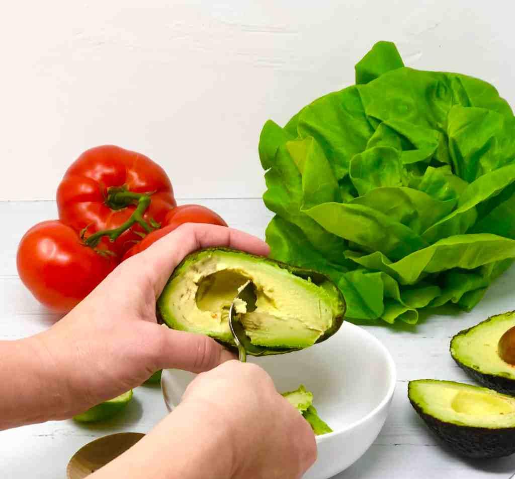 Scooping avocado into a bowl.