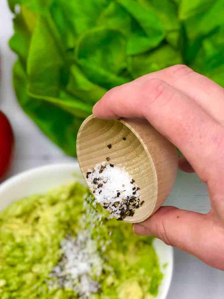 Adding salt and pepper to avocado.