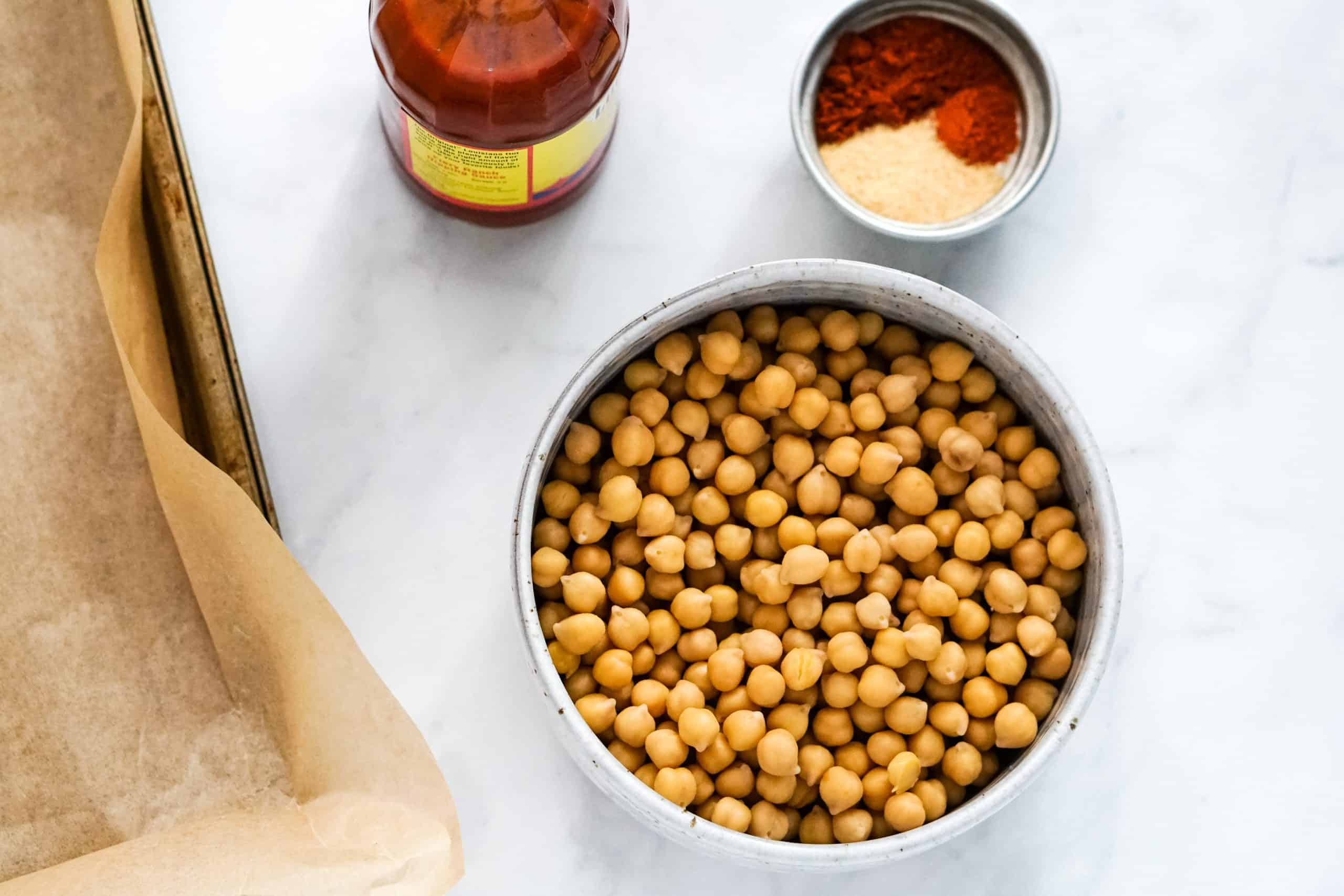 Chickpeas, spices and hot sauce on white table.