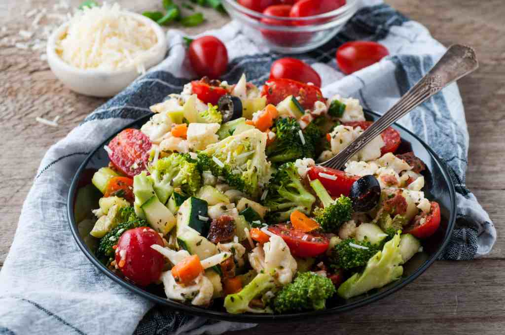 Crunch salad with fork in it on wood background with a bowl of Parmesan cheese and cherry tomatoes in the background.