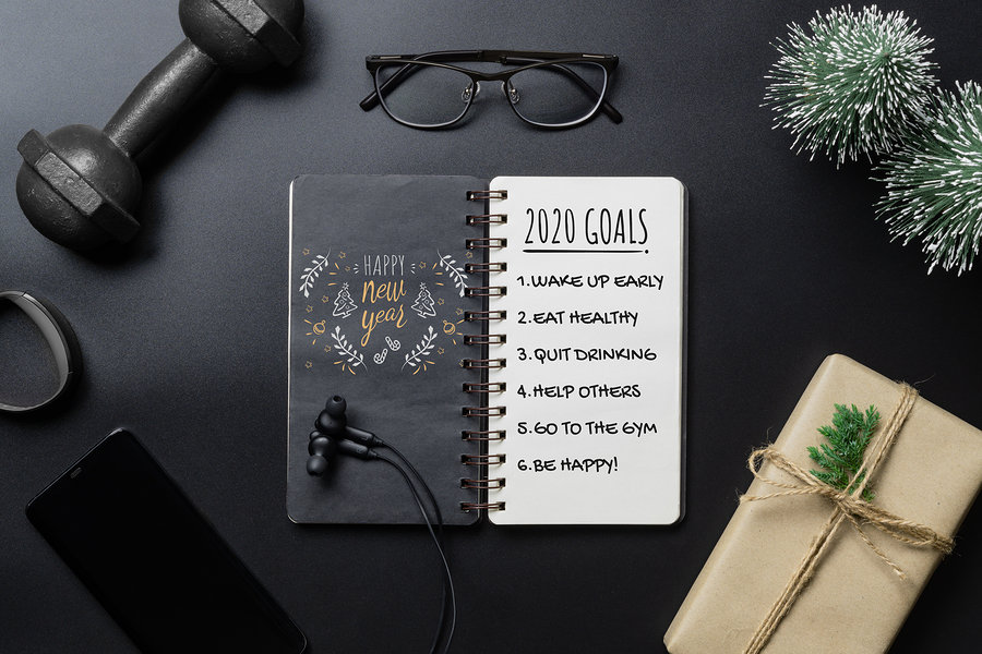 New Year Healthy Goals and Resolutions concept. 2020 New Year's Goals written on Notebook Paper, and dumbbells on black Background, Fitness, Sport and Health Concept, Top View