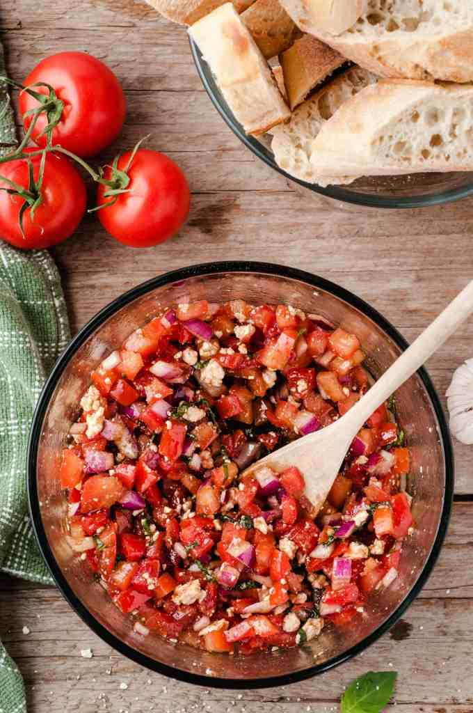 Bruschetta ingredients in a glass bowl with a wooden spoon in it.
