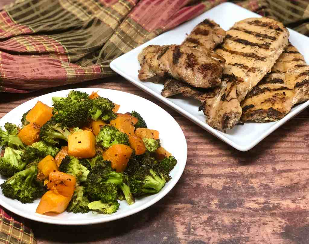 Roasted broccoli and sweet potatoes on a plate with grilled chicken behind it.