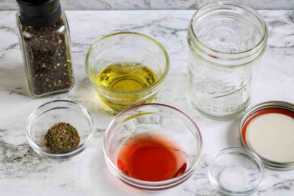 Black pepper, olive oil, red wine vinegar, salt and a mason jar on a white marble background.