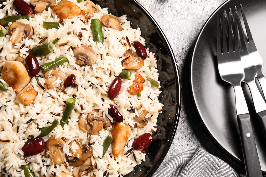 Delicious rice pilaf with chicken and vegetables on grey table, closeup