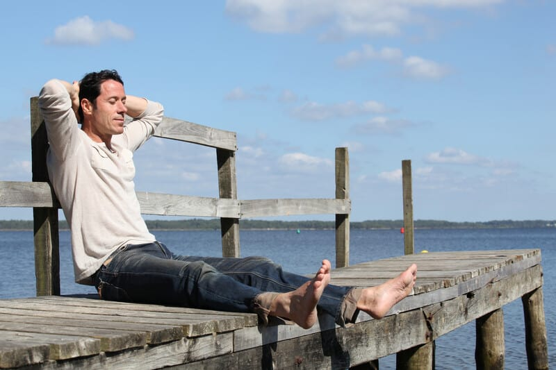 Man sitting alone on a dock with his eyes closed, looking happy and peaceful with hands behind his head resting.