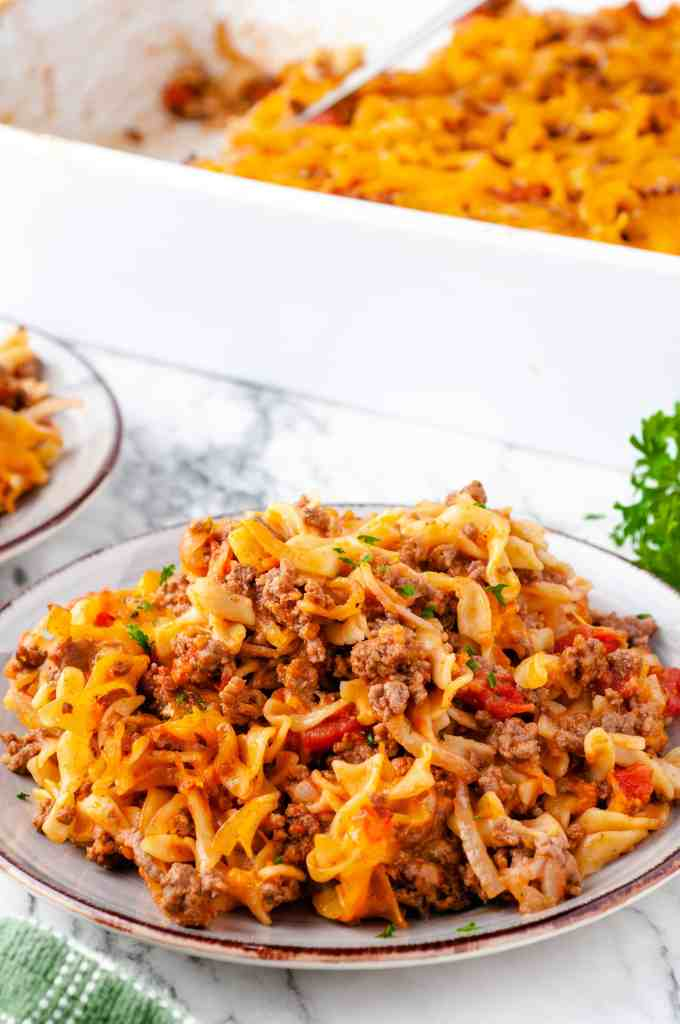Cheesy Beef and Noodle Casserole on a plate with a baking dish with the casserole in it in the background.