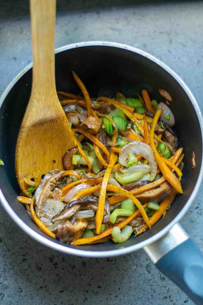 Carrots, onion, garlic, Bok Choy stems and shiitake mushrooms in a frying pan.