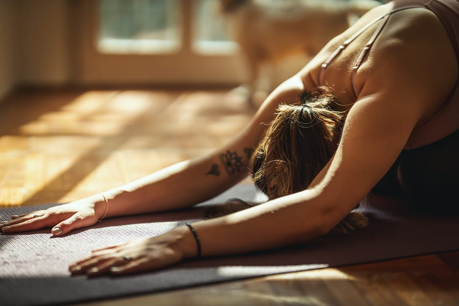 Young woman is doing yoga meditation in the living room at home. She is meditating on floor mat in morning sunshine.