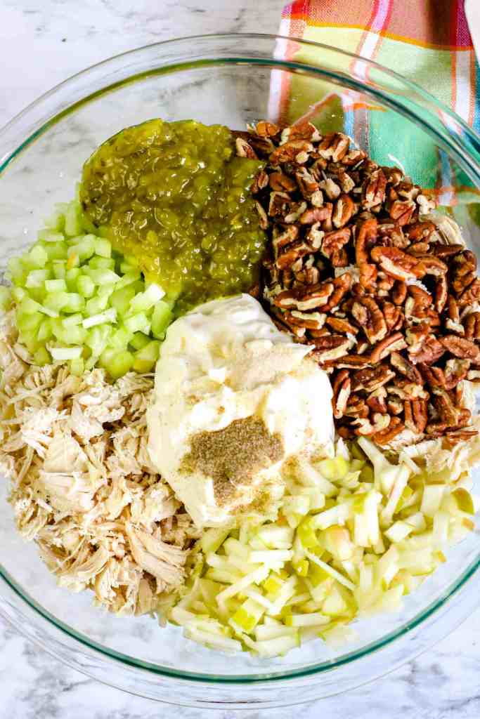 Overhead shot of chicken salad ingredients in a glass bowl.
