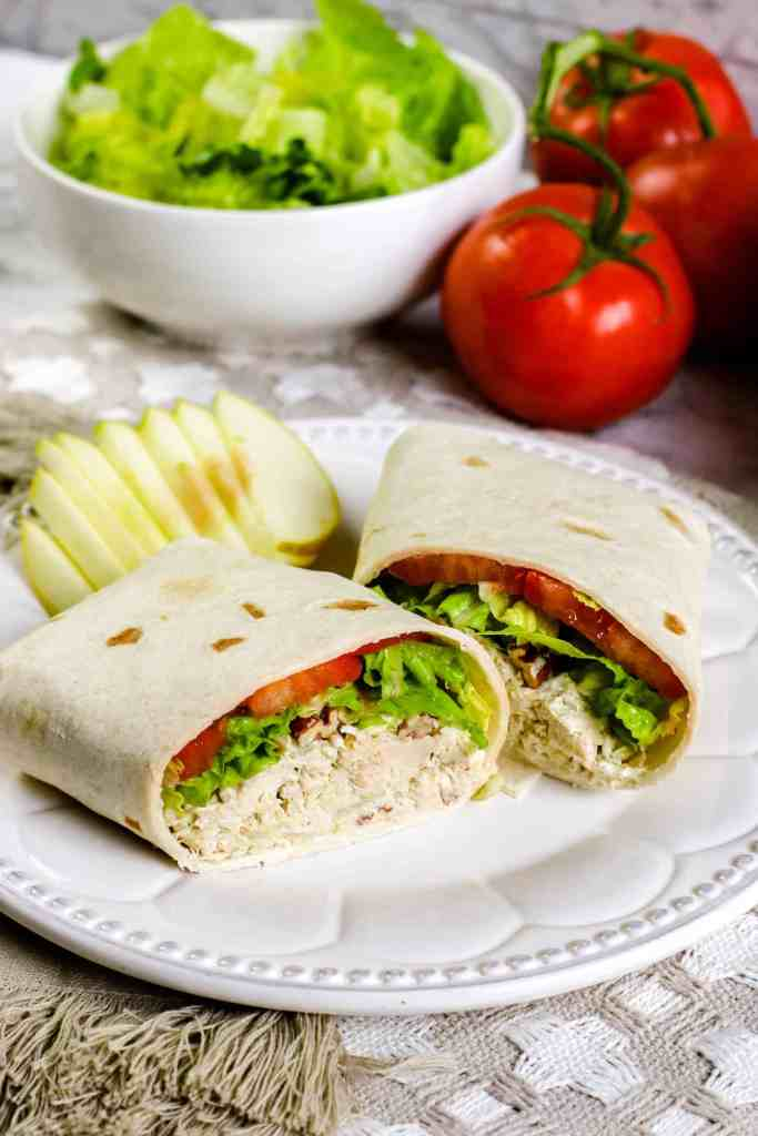 Chicken salad wrap on a white plate with sliced apples on the side and a bowl of lettuce and two red tomatoes in the background.