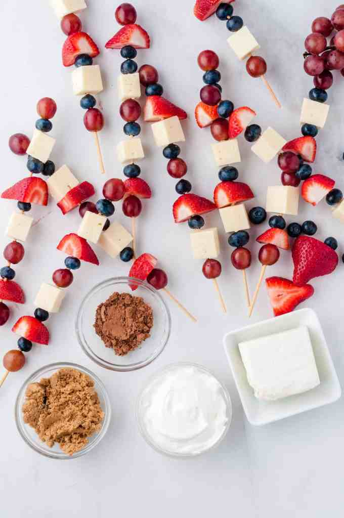 Overhead view of fruit kabobs and ingredients for cream cheese dip