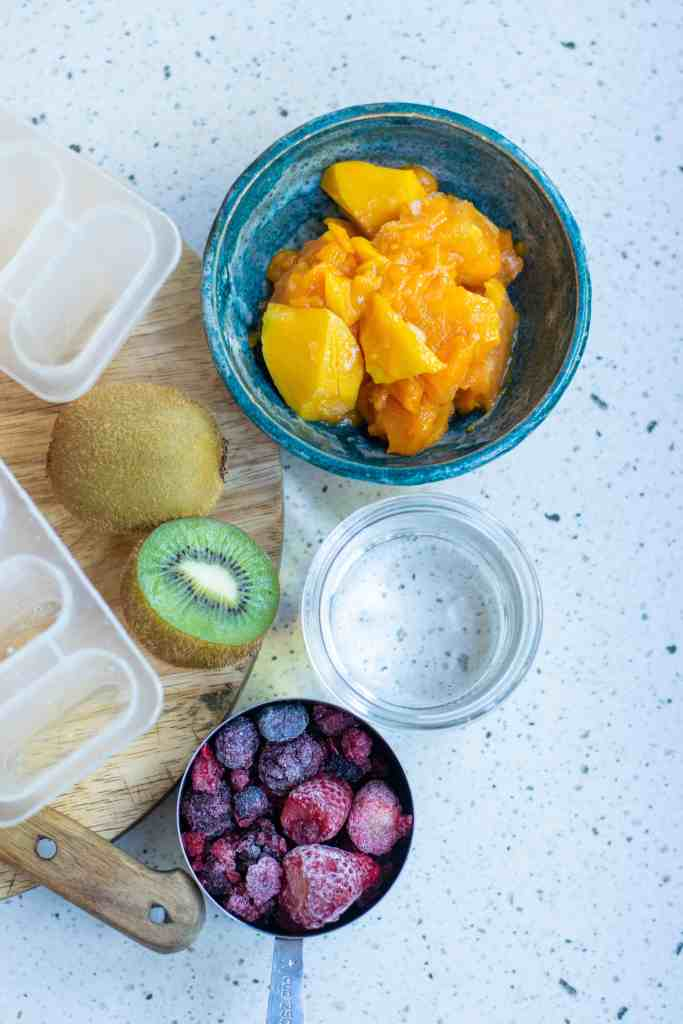 Mango chunks, frozen berries, kiwi, popsicles molds and glass bowl of water.