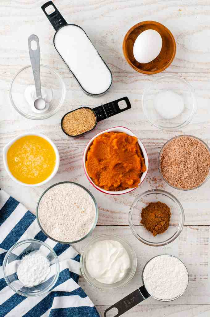 flour in a measuring cup, egg in a wood bowl, brown sugar in a measuring spoon, melted butter in a white bowl, brown sugar in a glass bowl, cinnamon in a glass bowl, wheat flour in a measuring cup, wheat germ in a glass bowl and pumpkin puree in a white bowl.