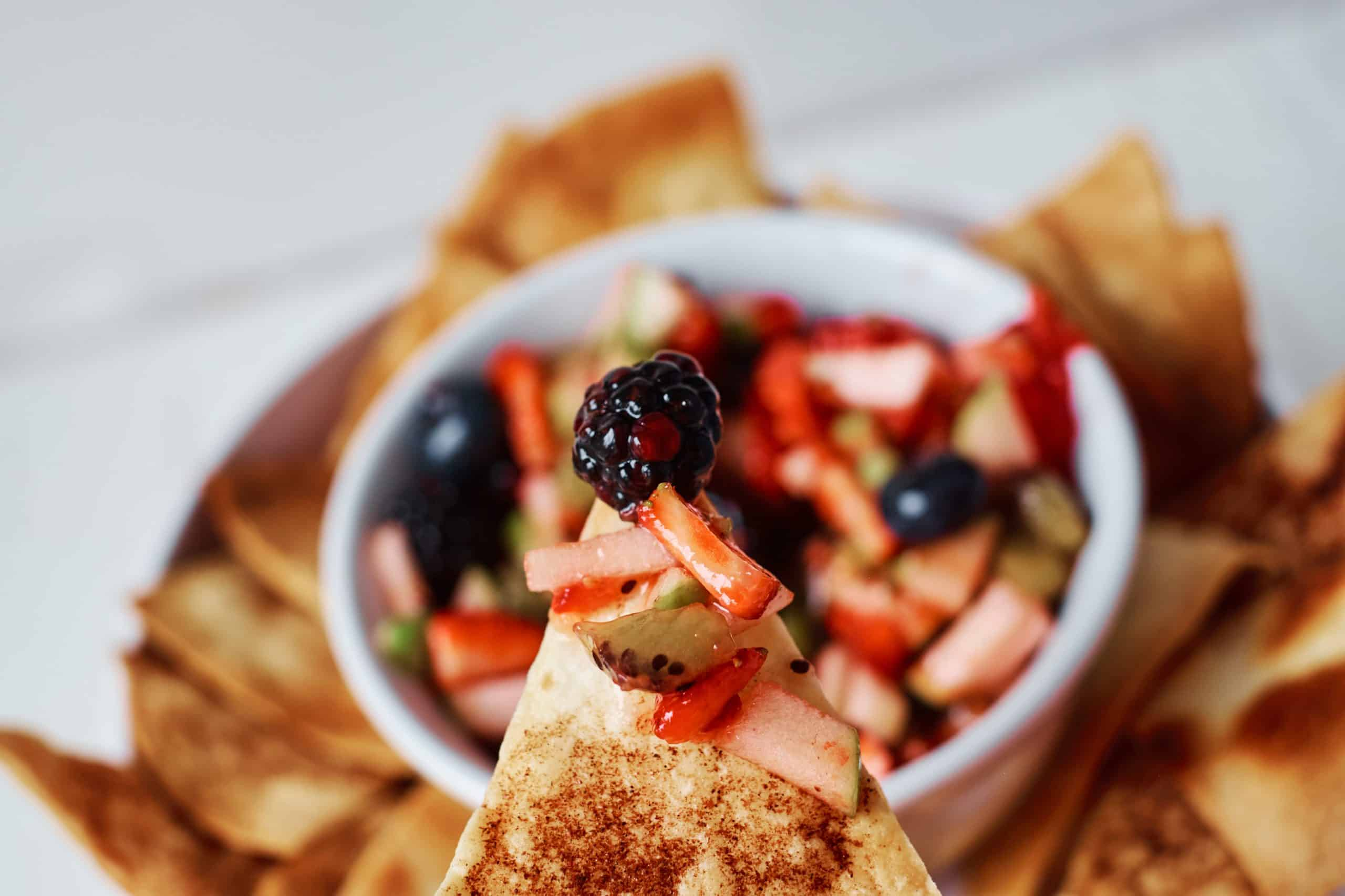 closeup of cinnamon tortilla chip with fruit salsa on it.