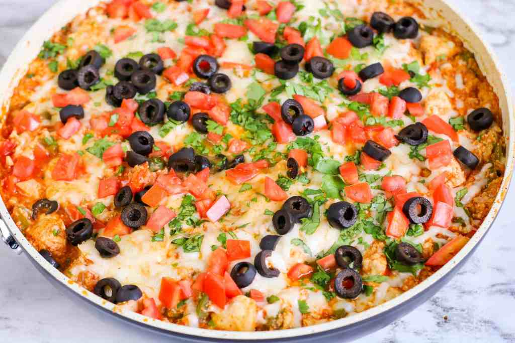 Tex Mex Chicken with Cauliflower Rice in a sauté pan, topped with black olives and cilantro.