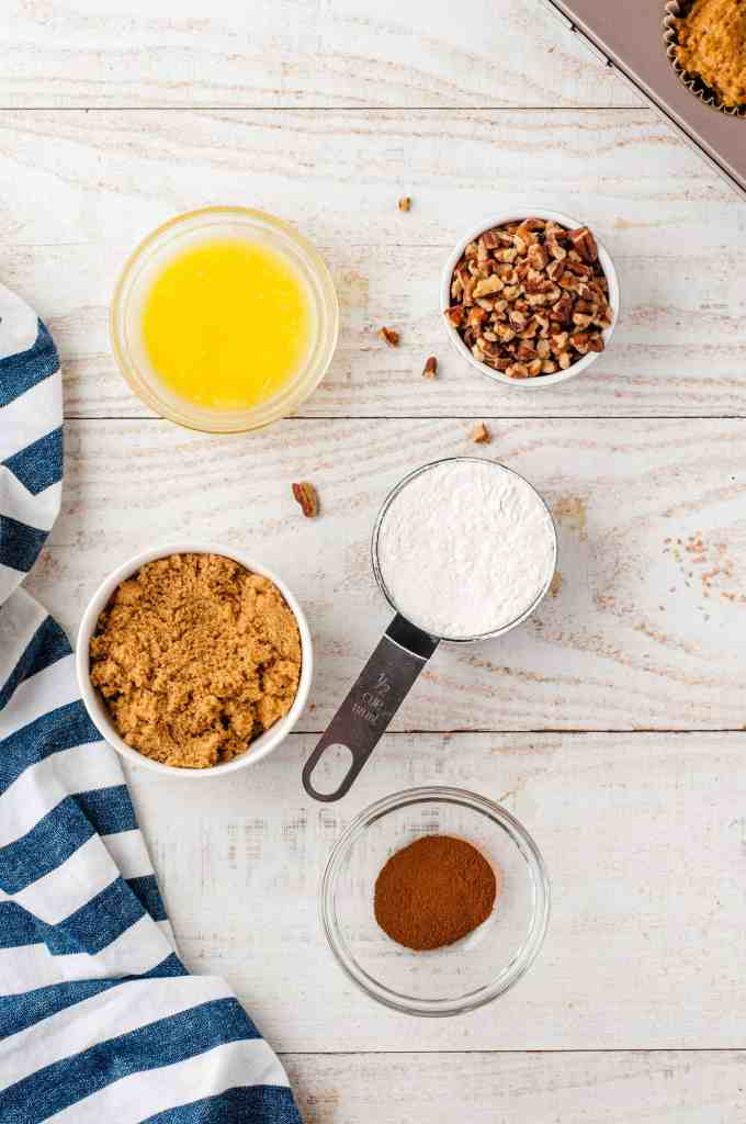 Melted butter in a glass bowl, brown sugar in a white bowl, flour in a measuring cup, cinnamon in a glass bowl and pecans in a white bowl on a white wood background.