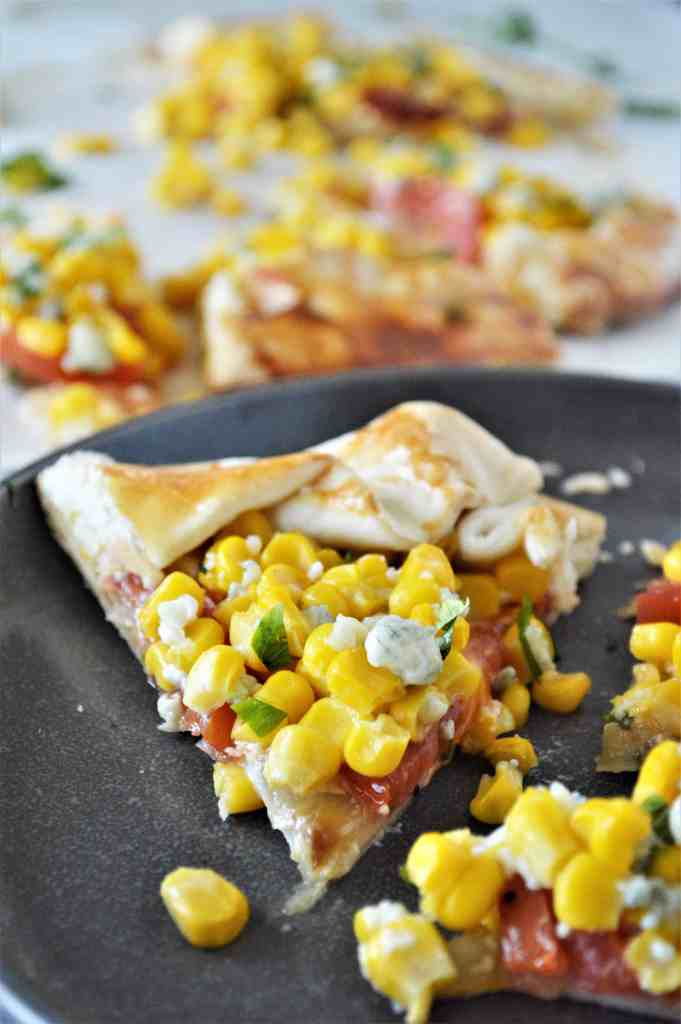 Savory Corn and Tomato Galette on a black plate.