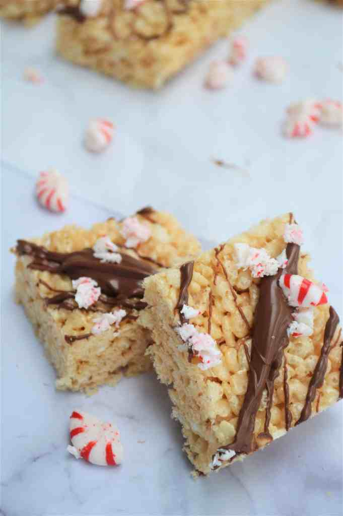 Two Rice Krispie treats with drizzled chocolate and crushed peppermint candies.