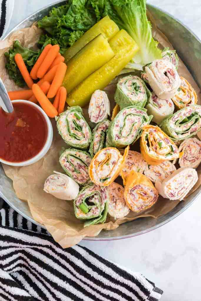 Easy Party Pinwheels on a platter with pickles, carrots, salsa and green leafy lettuce