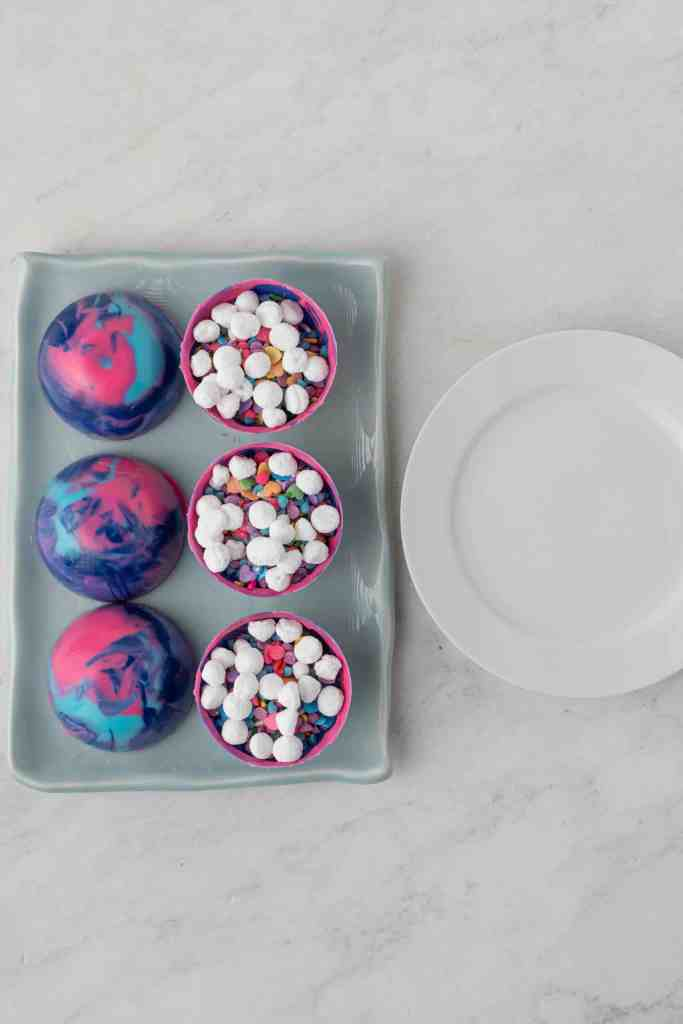 Galaxy hot cocoa bombs being prepared with mini marshmallows on top.