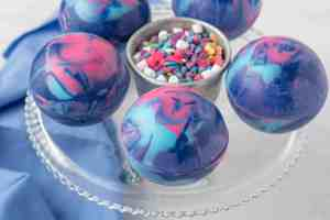 3/4 angle view of galaxy hot cocoa bombs on a glass cake stand.