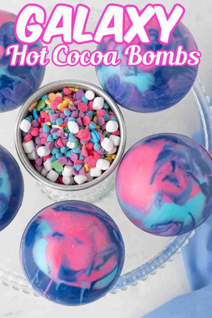Overhead photo of Galaxy Hot Cocoa Bombs with multi colored sprinkles in the center and text overlay.