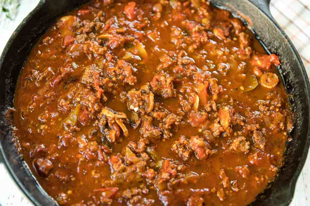 Closeup of meat sauce in a black iron skillet.
