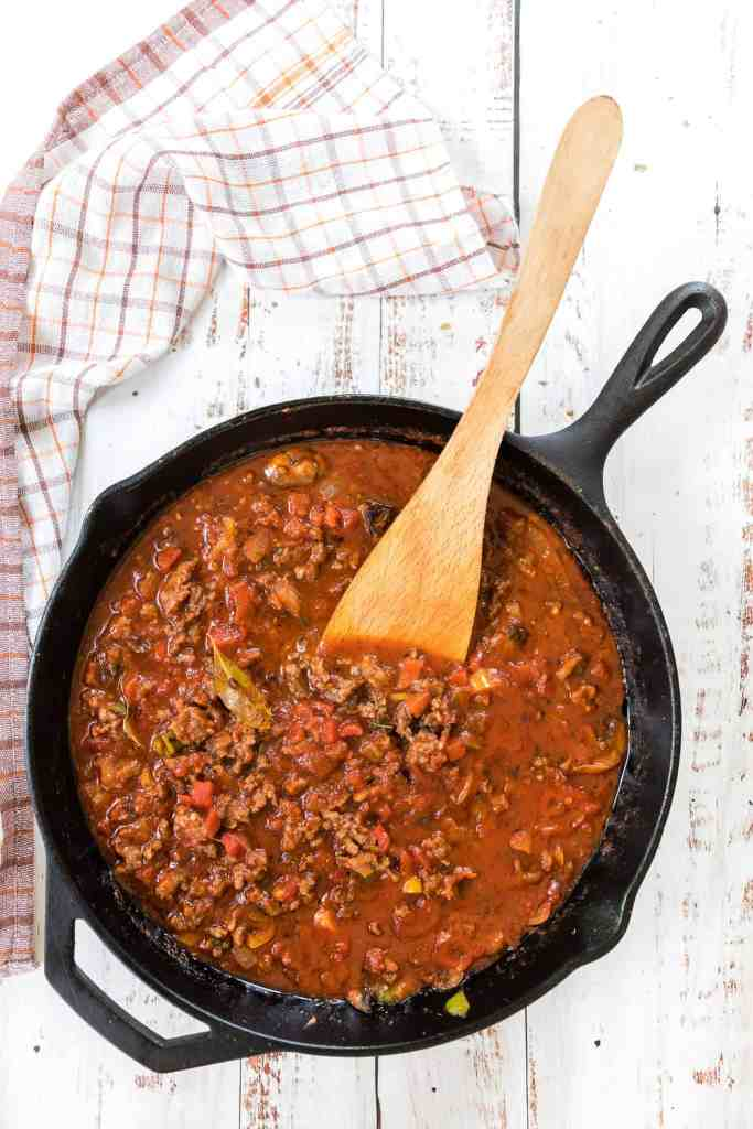 Homemade meat sauce in a black iron skillet with a wooden spoon.