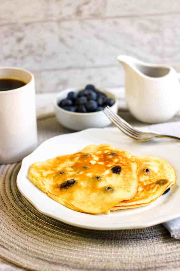 Blueberry pancakes on a white plate with a bowl of blueberries behind it and a creamer pitcher.