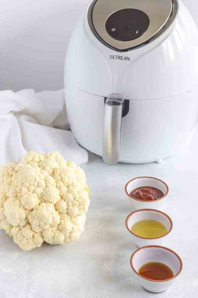 White air fryer with cauliflower and spices.