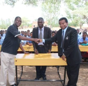 Kadango L officially handing over the desks to South East Education Division Manger Mc Gregory Alufandika while the deputy teacher looks on