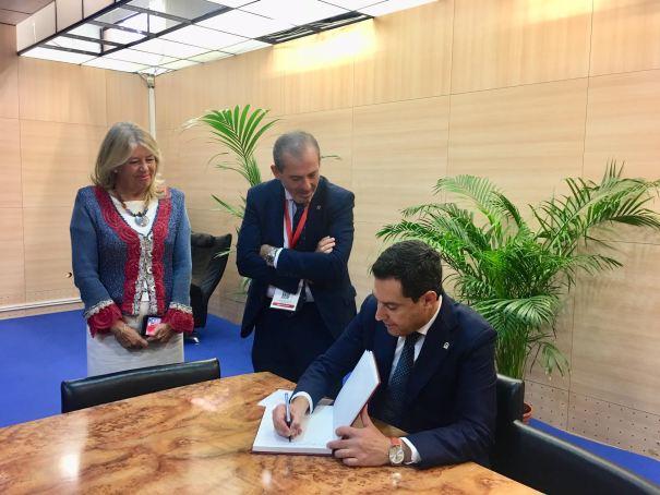 El presidente de la Junta, Juanma Moreno, firma en el libro de honor del ICA este viernes, en presencia de la alcaldesa de Marbella, Ángeles Muñoz y el decano del ICA, Francisco Javier Lara. FOTO/ CABANILLAS