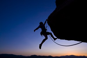 Climber dangling against sunset horizon.