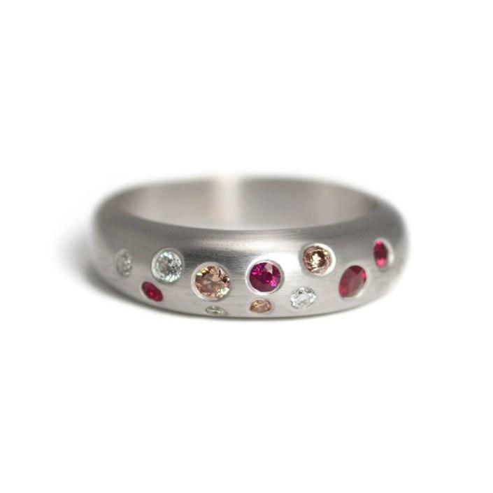 Witgouden ring, bezet met robijnen, bruine en witte diamanten.
