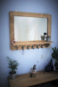 Set against a pale blue painted wall, this beautiful modern rustic wall mirror with shelf and 5 black cast iron hooks features a solid, thick reclaimed wooden frame in pale Danish Oil. Handmade to order by Marc Wood Joinery UK. View our rustic furniture collection in our online shop, available to order. This mirror with shelf is useful for your hallway storage and bathroom, bedroom use.