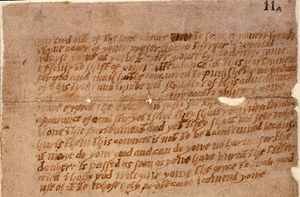 A damaged and aged piece of paper, or parchment, with multiple lines of handwritten English text.